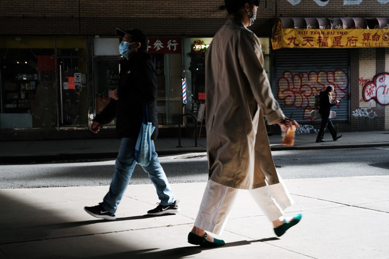 Image: People walk through the streets of Chinatown on March 23, 2021 in New York City.