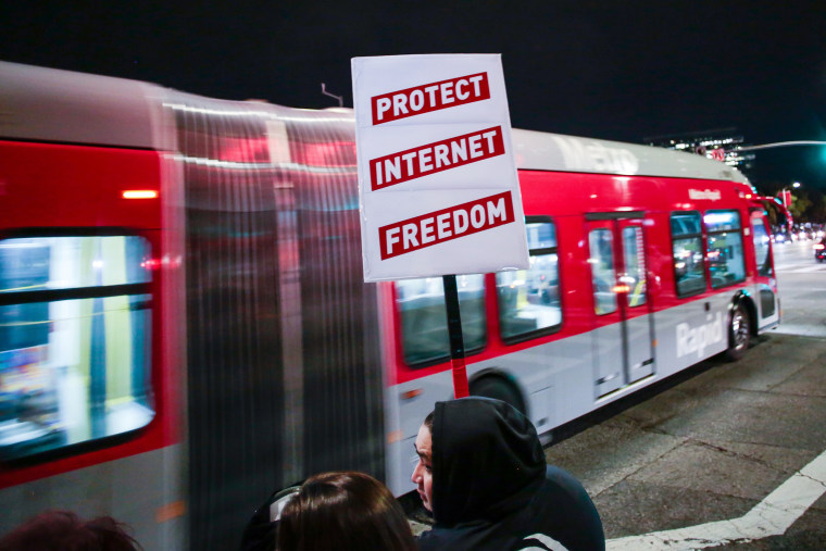 A supporter of Net Neutrality protests the FCC's recent decision to repeal the program in Los Angeles