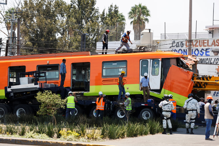 Workers assess a damaged train car after it was moved from a site where an overpass for a metro partially collapsed with train cars on in Mexico City on May 4, 2021.