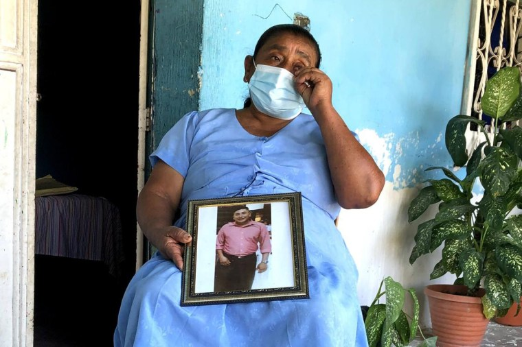 Image:; Martha Nájera holds a photo of her son Gustavo Nájera, who was murdered along with 8 other migrants from San Pedro Pinula.