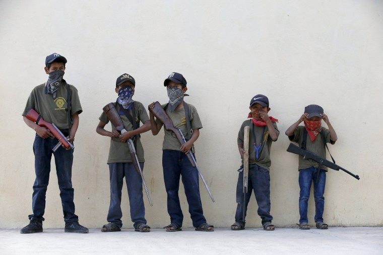 Image: Children hold their training weapons, some real and some fake, during a display for the media