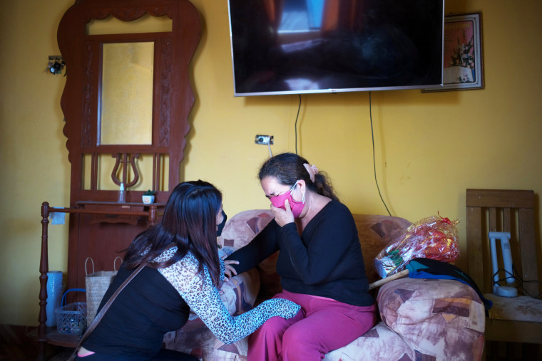 Hellen Nanez, who lost 13 relatives to Covid-19 and whose father Guillermo Alejandro Nanez is being treated the disease, comforts her aunt Paulina Nanez after telling her that Guillermo's condition has worsened in Pisco, Peru, on May 10, 2021.