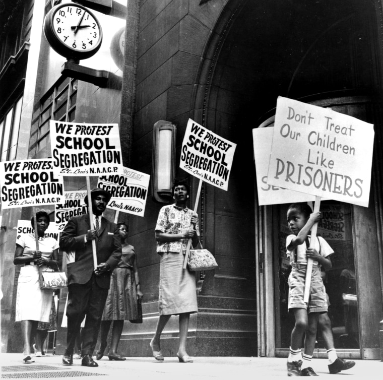 Demonstrators picket in front of a school board office in protest of segregation, in St. Louis, Mo., early 1960s.