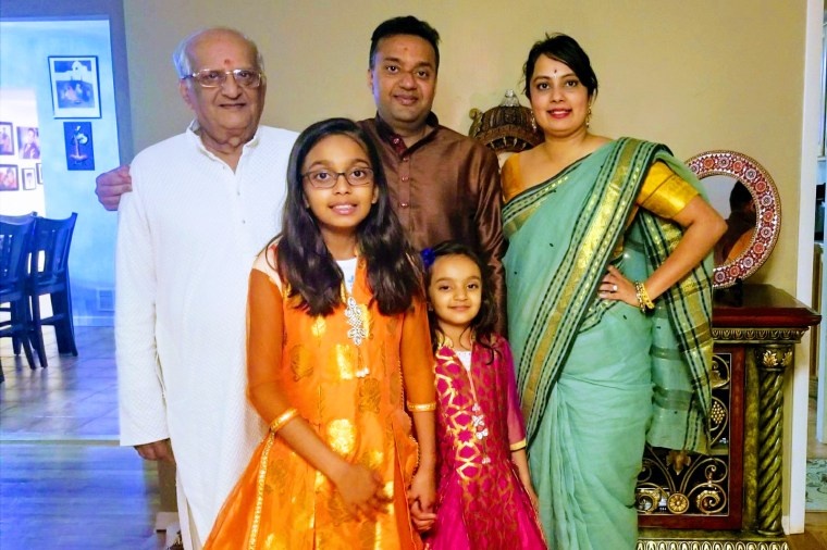 Ashu Mahajan, center, with his wife Neha, his father and his children.