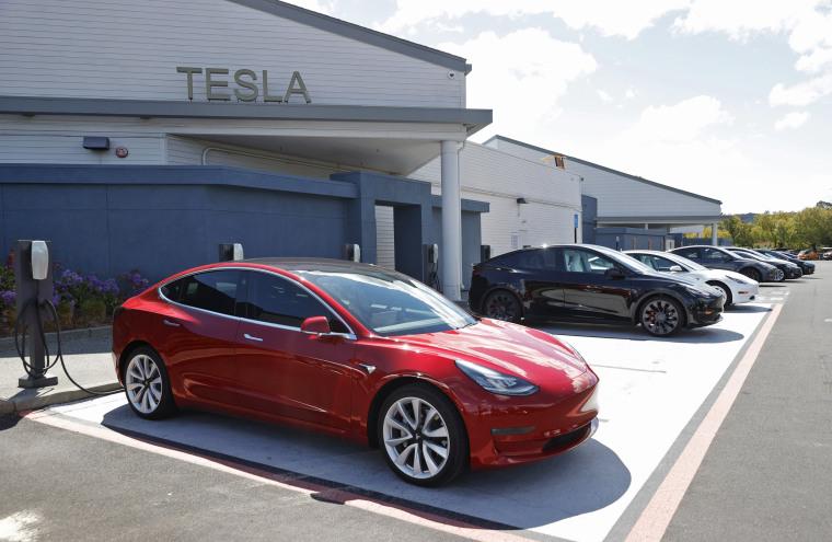 Image:  Tesla cars charge at a Tesla Supercharger station on April 26, 2021 in Corte Madera, Calif.