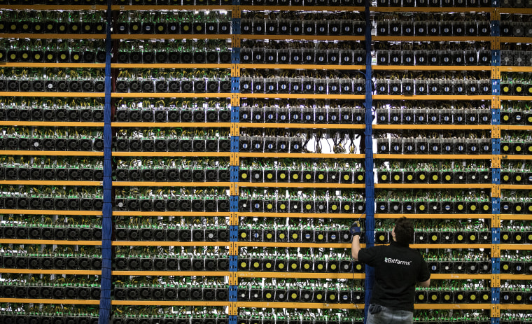 Image: An employee checks fans on mining machines at a cryptocurrency farming facility in Farnham, Quebec, Canada, on  Jan. 24, 2018.