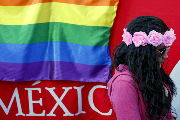 A woman walks past a rainbow flag hung on the outside of a tent offering free HIV testing, part of events to mark International Day Against Homophobia, Transphobia and Biphobia, in the Alameda park in central Mexico City on May 17, 2018.
