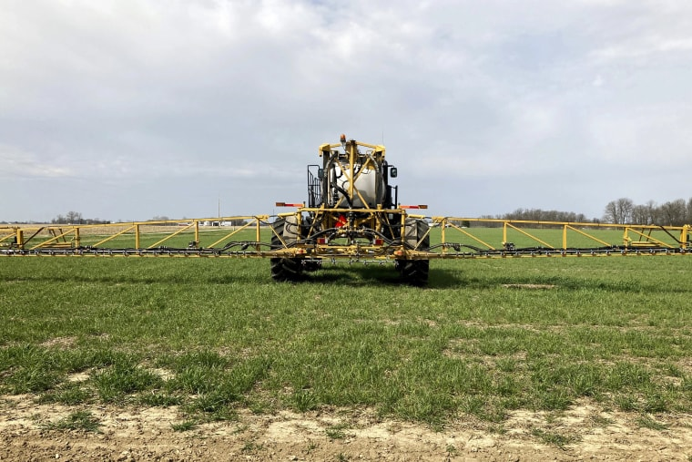 Farmer Rick Clifton drives a spray tractor across one of his fields, applying herbicide to cover crops in Orient, Ohio, on April 5, 2021.