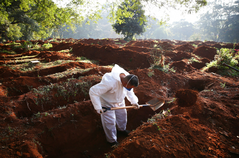 Image: A cemetery worker digs a grave shortly before the bodies of people who died of Covid-19 arrive for burial at the Vila Formosa cemetery on May 19, 2021 in Sao Paulo, Brazil.
