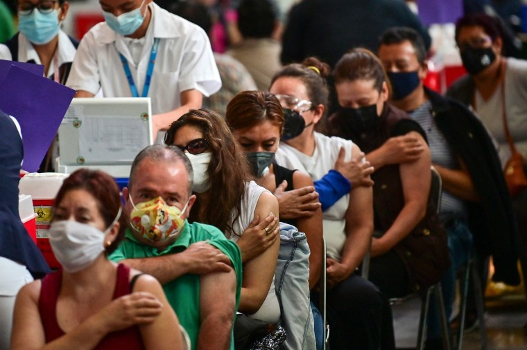 Image: People wait after receiving doses of the Pfizer-BioNTech vaccine  at a vaccination center at the Vasconcelos Library, in Mexico City