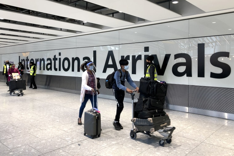 Passengers are escorted through the arrivals area of terminal 5 towards coaches destined for quarantine hotels, after landing at Heathrow airport on April 23, 2021 in London.