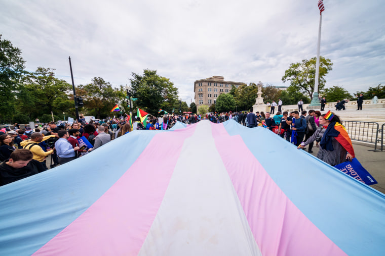 Protesters unfurl a giant transgender pride flag outside the Supreme Court in Washington on Oct. 8, 2019.