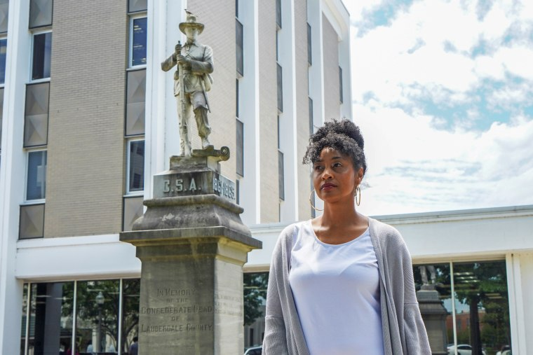 Camille Bennett poses for a photo in front of the confederate statue that she is trying to have moved to the confederate cemetery in Florence, Ala., on May 19, 2021.