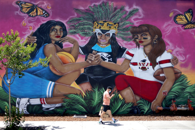 A man walks past a mural in East Los Angeles on May 26, 2021.