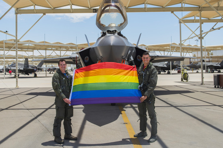 Maj. Tyler McBride and Capt. Justin Lennon hold a Pride flag after a Pride Month flyby on June 26, 2020, at Luke Air Force Base, Ariz.
