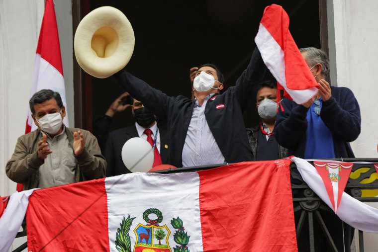 Presidential candidate Pedro Castillo holds a national flag from a balcony of the Peru Libre party's headquarters in Lima on June 7, 2021, a day after runoff elections.
