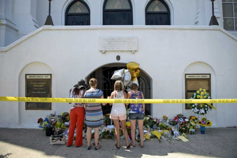 Mourners gather at a makeshift memorial outside the Emanuel AME Church in Charleston, S.C.,  on June 18, 2015, after a mass shooting at the church the night before.