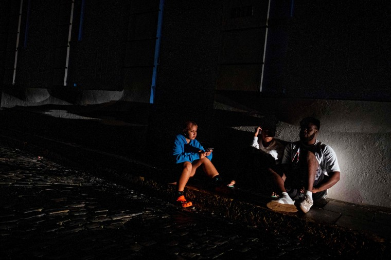 People sit on the sidewalk of a street left in darkness by a power outage due to a cyberattack in Old San Juan, Puerto Rico, on June 10, 2021.