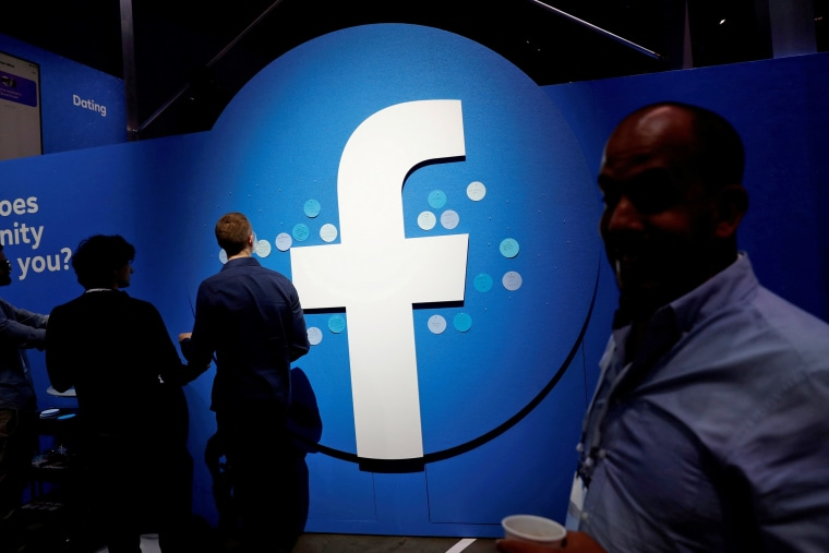 Image: FILE PHOTO: Attendees walk past a Facebook logo during Facebook Inc's F8 developers conference in San Jose
