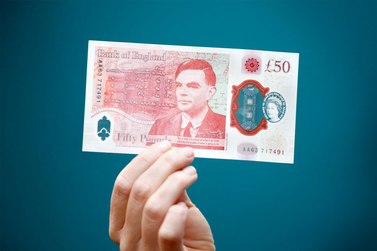 Sarah John, chief cashier of the Bank of England holds up  a new 50-pound banknote with the face of World War II codebreaker Alan Turing at Daunt Books in London on June 23, 2021.