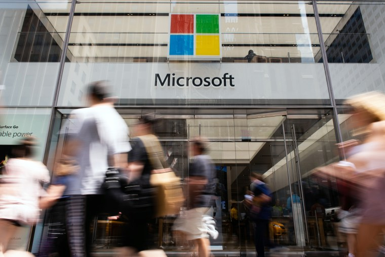 Image: Pedestrians pass in front of the Microsoft Corp. flagship store in New York City on July 14, 2018.