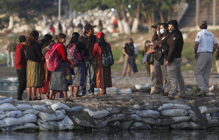 Image: Mexican immigration agents review the IDs of Guatemalan travelers at an access point to the Suchiate River, on the border between Guatemala and Mexico, near Ciudad Hidalgo, Mexico.