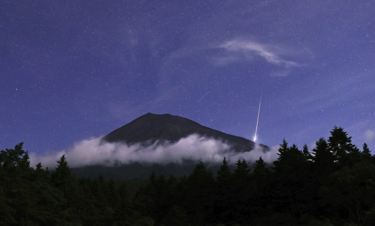 A meteor streaks across the sky above Mount Fuji in Fujinomiya in Shizuoka prefecture in Japan during the annual Perseid meteor shower Aug. 13.