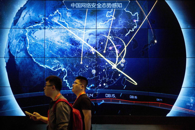 Attendees walk past display showing recent cyberattacks in China at the China Internet Security Conference in Beijing on September 12, 2017.