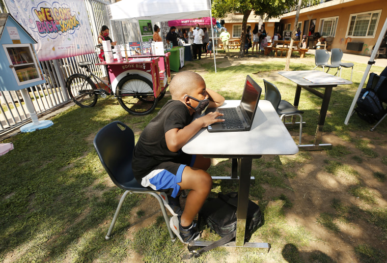 A student works on a laptop computer with other kids studying outdoors in the motel plaza area at Hyland Motel in Van Nuys, Calif., on Aug. 24, 2020.