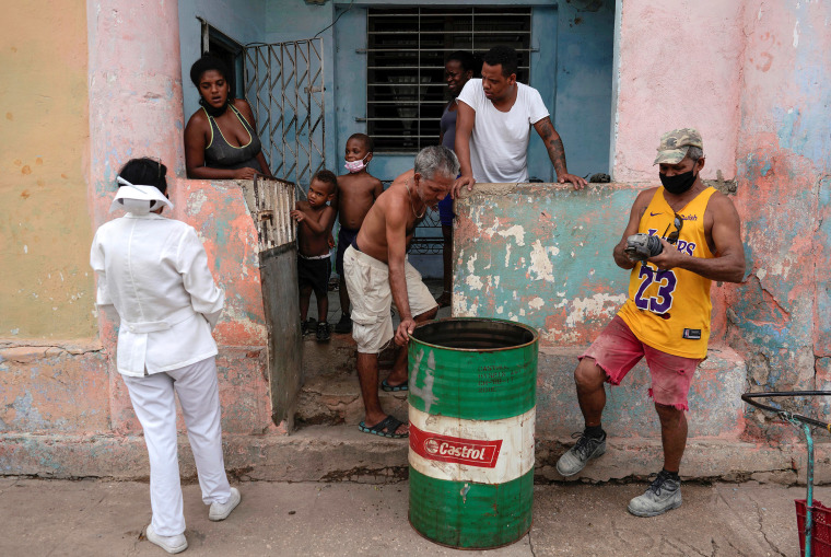 Image: A nurse asks a family to go to a vaccination center in Havana