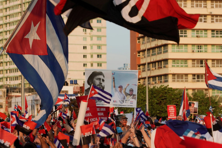 People carry a poster with photographs of Fidel Castro, President Miguel Diaz-Canel and former president Raul Castro during a rally in Havana on July 17, 2021.