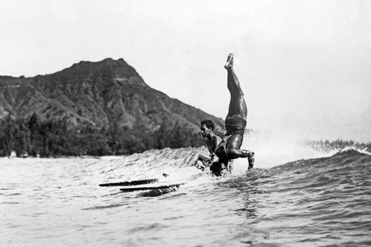Image: A surfer at Waikiki Beach stands on his head as he rides a wave into the shore in Honolulu c. 1925.