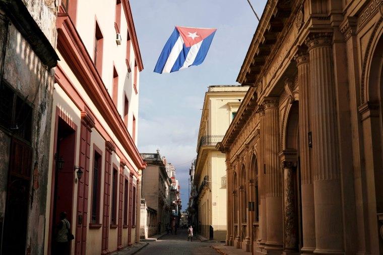 Image: A Cuban flag flies over a street in downtown Havana
