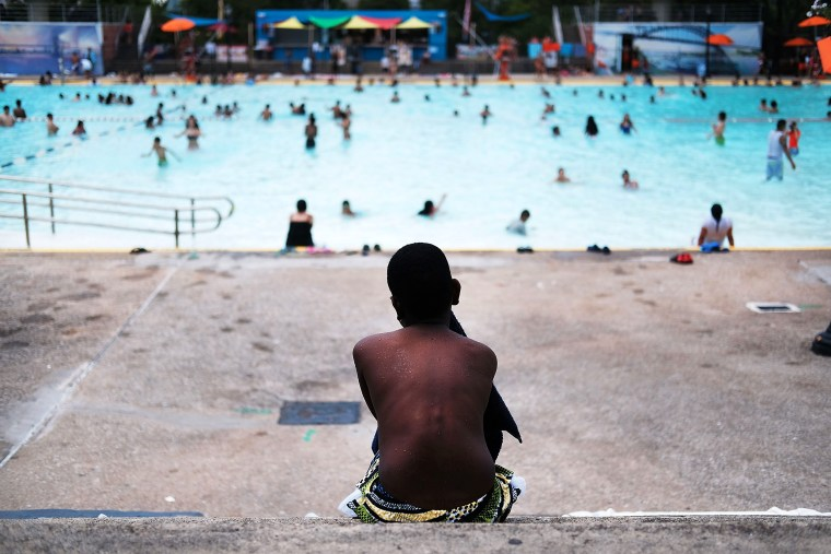 Image: A child takes a break from swimming at the Astoria Pool in Queens, N.Y., on June 29, 2016.