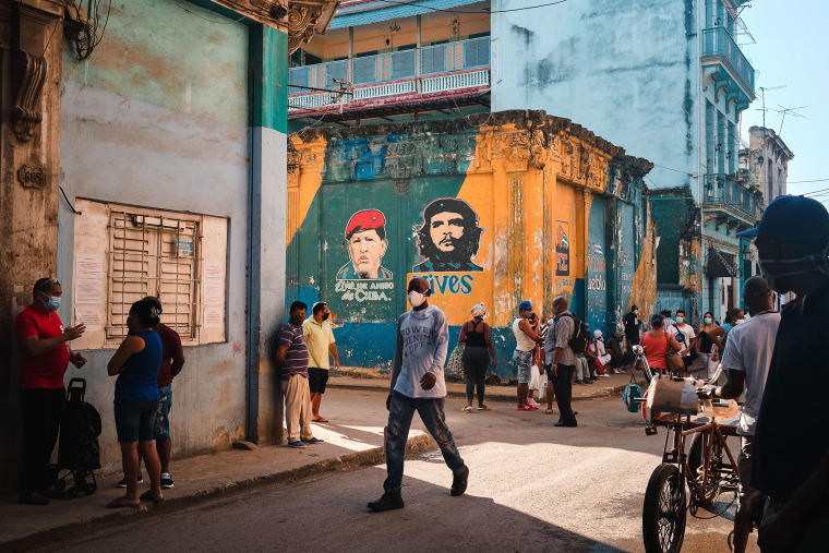 Image: Customers wait in line to enter a grocery store in Havana on July 13, 2021.