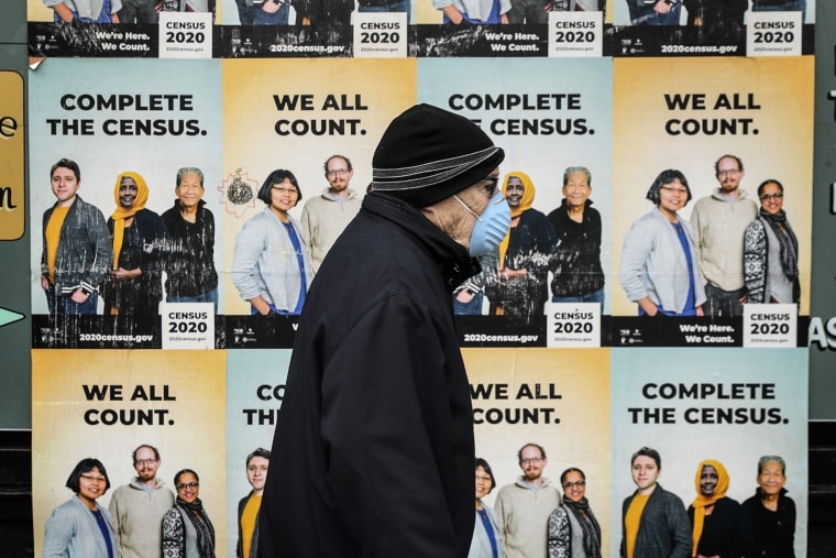 A man walks past posters encouraging participation in the 2020 Census in Seattle's Capitol Hill neighborhood on April 1, 2020.