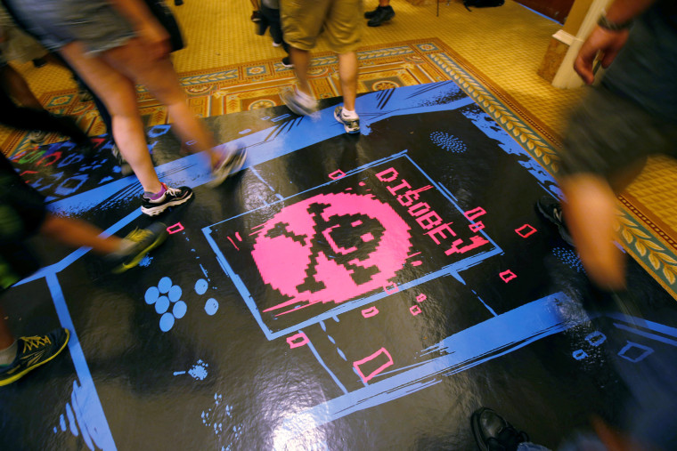 People walk past a floor graphic during the Def Con hacker convention in Las Vegas