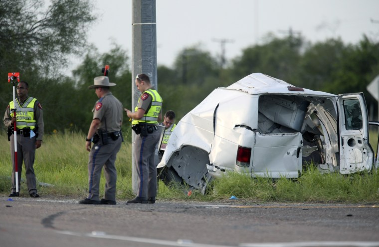 Image: Texas Department of Public Safety officers stand near a van that crashed into a utility pole on Aug. 4, 2021, in Encino, Texas.