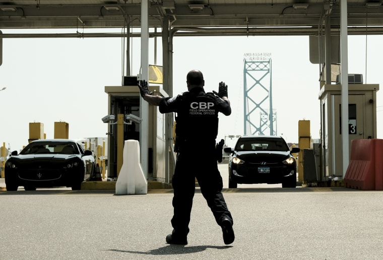 Image: U.S. Customs and Border Protection agents direct vehicles re-entering the U.S. from Canada, which has opened its borders to U.S. citizens who can provide proof of vaccination and a negative Covid-19 test, for random searches and inspections at the Ambassador Bridge Port of Entry Aug. 9, 2021 in Detroit.