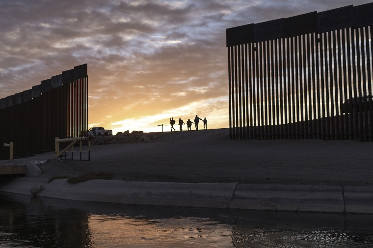 A pair of migrant families from Brazil pass through a gap in the border wall to reach the United States after crossing from Mexico in Yuma, Ariz., on June 10, 2021, to seek asylum.