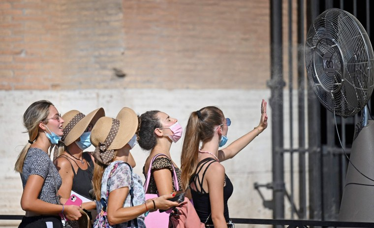 Visitors at the Colosseum in Rome cool off in front of a fan Thursday.