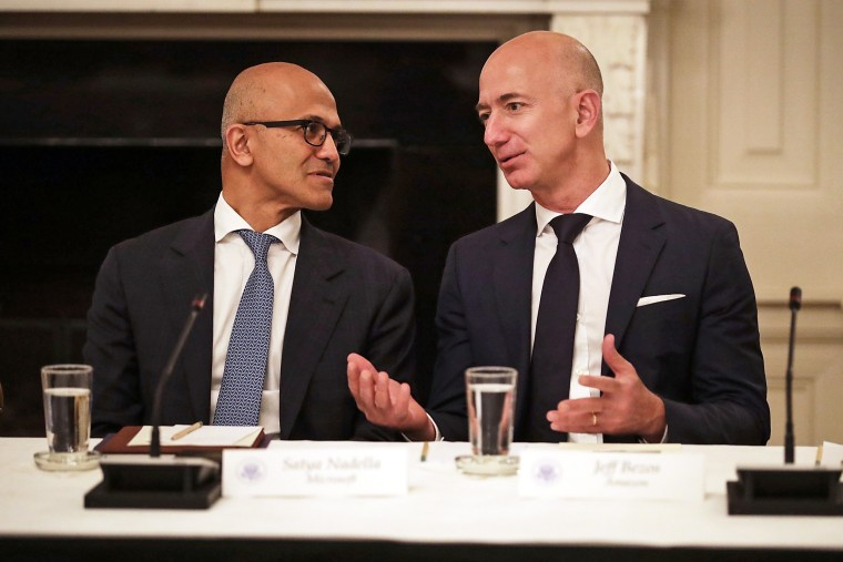 Microsoft CEO Satya Nadella and Amazon CEO Jeff Bezos talk with each other before a meeting of the White House American Technology Council in Washington on June 19, 2017.