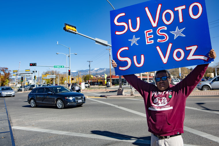 """A man holds a Spanish-language sign, """"Your vote is your voice,"""" during the midterm elections in Santa Fe, N.M., on  Nov. 6, 2018."""