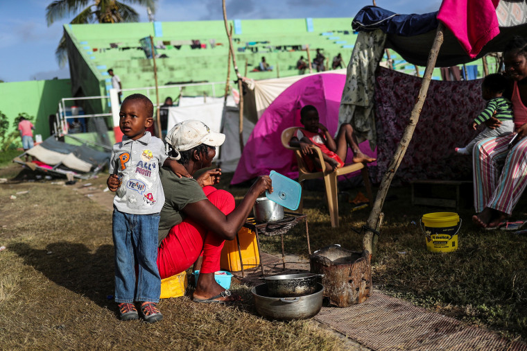 Image: An evacuated woman prepares breakfast in Les Cayes