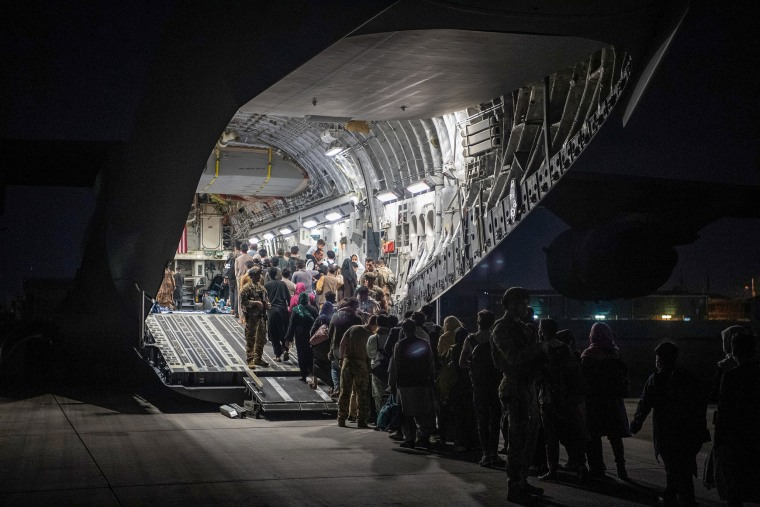 Image: Afghans board a U.S. Air Force C-17 Globemaster III transport plane during an evacuation at Hamid Karzai International Airport, Afghanistan on Aug. 22, 2021.