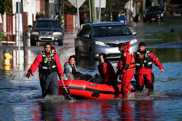 First responders pull local residents in a boat as they perform rescues of people trapped by floodwaters after the remnants of Tropical Storm Ida brought drenching rain,  flash floods and tornadoes to parts of the northeast in Mamaroneck, N.Y., on Sept. 2, 2021.