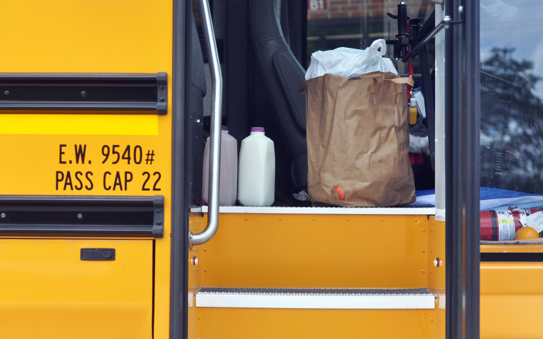 Buses bring prepared hot meals to pickup sites for families to pickup once a week through the summer, around Gurnee, Ill., on June 29, 2021.