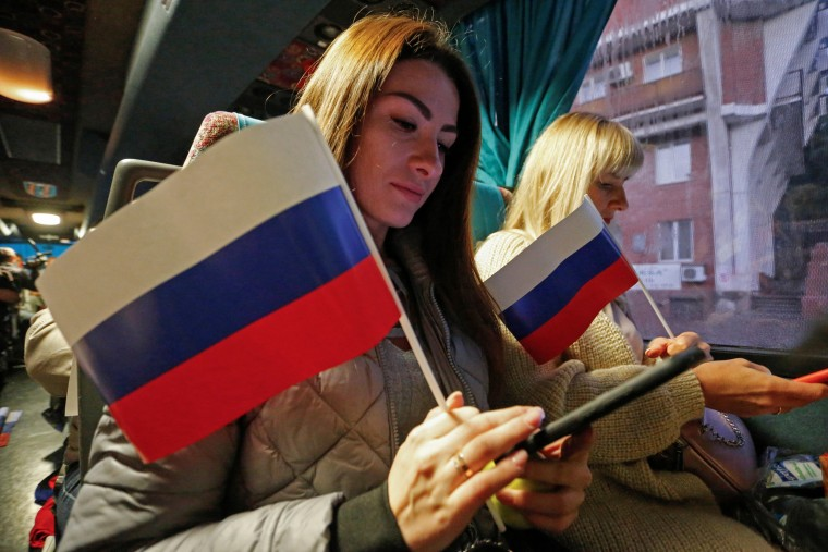Image: People board a bus to vote in the Russian parliamentary election in the rebel-held city of Donetsk