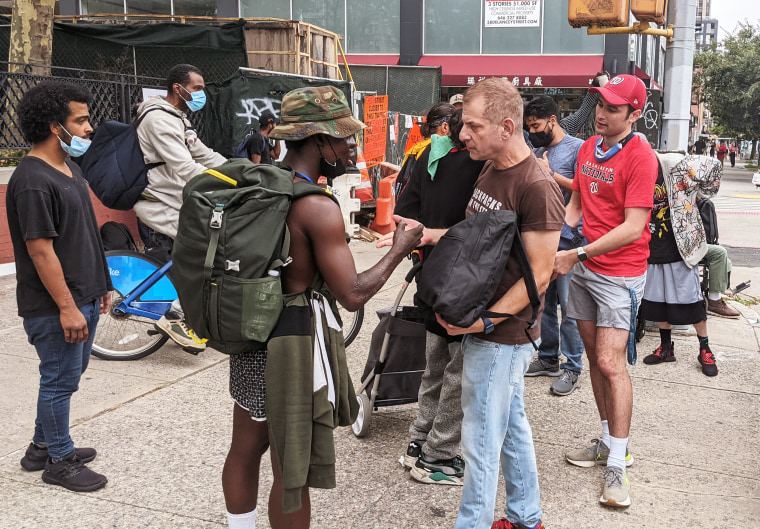 Jeffrey Newman, second from right, hands out backpacks to those experiencing homelessness in New York, N.Y.