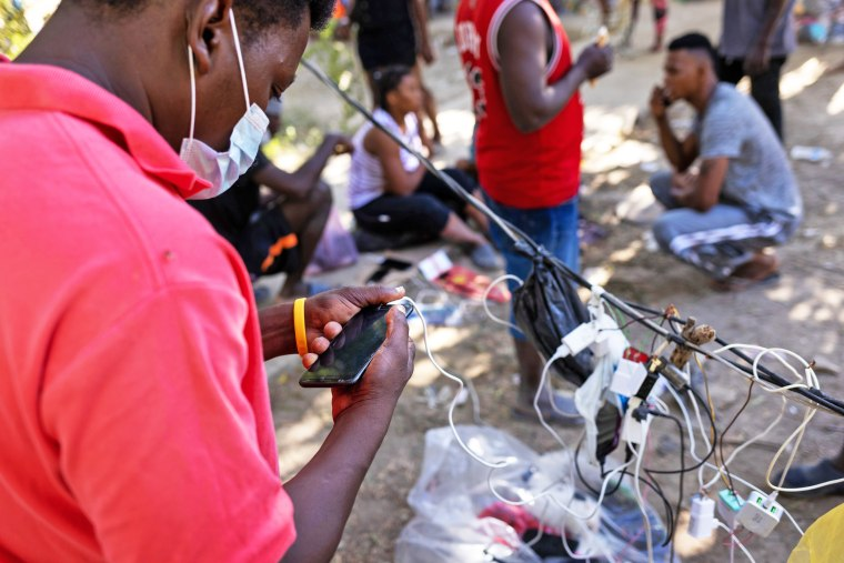 A Haitian immigrant charges his smartphone on Sept. 22, 2021, in Ciudad Acuna, Mexico.